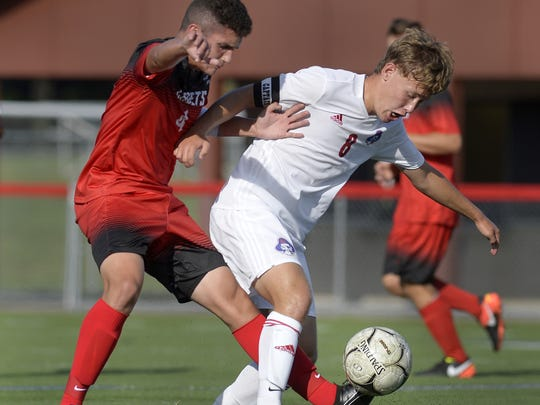 Fairport's Bobby Guilfoil, right, shields the ball from Hilton's Tom Callery during a regular season game at Fairport High School on Tuesday, Sept. 12, 2017. Fairport beat Hilton 1-0.