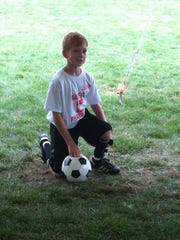 Candon Westervelt posing with a soccer ball in September 2014. He has played youth soccer since his operation.