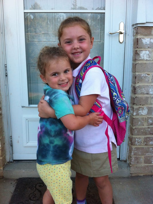 Amelia, 5, and Gabriella, 3.5, pose for the obligatory First Day of School photograph.