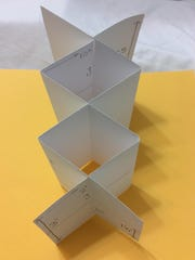 After adding slits, the two trapezoid shapes, each folded twice, fit into each other.