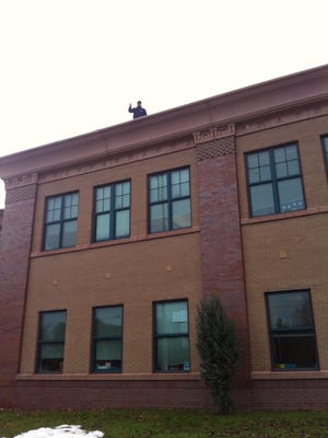 Jason Wertz, principal of School 45, stands on his school's roof. He had promised to spend a day on the roof if his students met a reading goal.