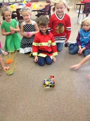 Woodside kindergarten students watch how a structure will react as the Big Bad Wolf (a big fan) blows against it.