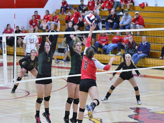 Wittenberg-Birnamwood blockers Madison Bushman (3) and Marissa Groshek put up a block against Pacelli's Paige Hintz during their Central Wisconsin Conference-8 match Tuesday night.