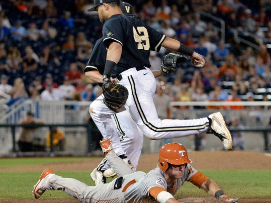 Texas' Madison Carter, bottom, tries to avoid the tag by sliding into first base but is out by Vanderbilt first baseman Zander Wiel (43) in the ninth inning of an NCAA baseball College World Series game in Omaha, Neb., Saturday, June 21, 2014. (AP Photo/Ted Kirk)