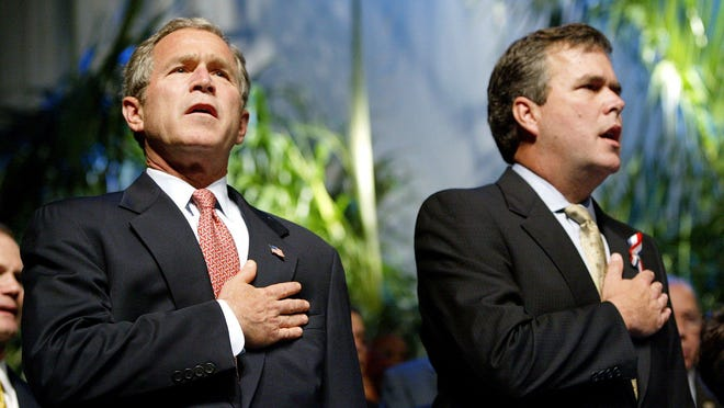 Then-President George Bush is joined by his brother, Jeb Bush, during a Cuban Independence Day event at the James L. Knight Center in Miami, Fla., in 2002.