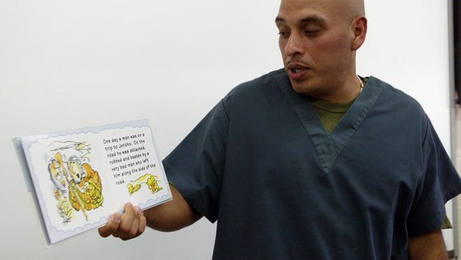 Christopher Ramirez practices reading aloud a story about the biblical parable of The Good Samaritan in a classroom at Kettle Moraine Correctional Institution on Wednesday, July 15. Ramirez completed the prison's For the Love of Reading Program that is meant to encourage early literacy skills in inmate's children.