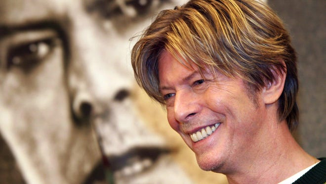 This file photo taken on September 10, 2002 shows British singer David Bowie smiling during a CD signing in Paris, ahead of his upcoming concerts in the French capital 24 and 25 September. This year the world of pop music has been moved by tears for the deaths of legends David Bowie, Prince and Leonard Cohen and seen the surprise Nobel prize for Bob Dylan. For certain the music of these legends will find themselves under the christmas trees of many, along with that of other, lesser known and more underground artists.