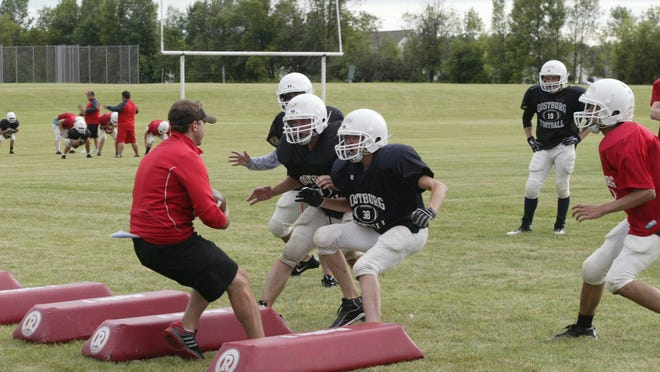 A group of Oostburg defenders swarm to Flying Dutchmen head coach Scott Ring while running through a drill at a recent practice.
