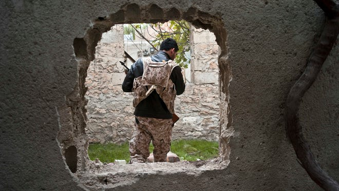 In this Nov. 1, 2014 photo, a fighter from the coalition against the Islamic State group is seen through a hole cut in a wall to create shortcuts in the battlefield in Kobani, Syria.
