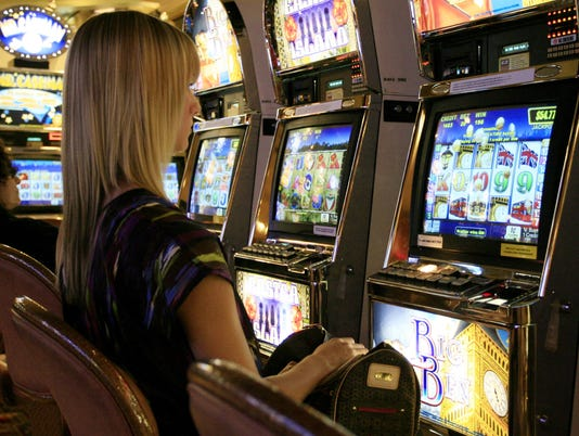 A tourist plays a slot machine while at