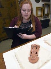 Mickaela Clark studies a Mayan artifact in the vault