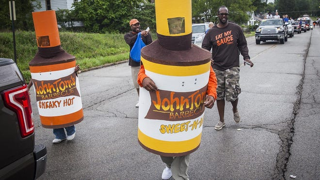 John Tom's Barbecue mascots walk the Muncie Homecoming Festival parade on Gavin Street Saturday morning. The parade traveled from the Debonair Club to McCulloch Park.
