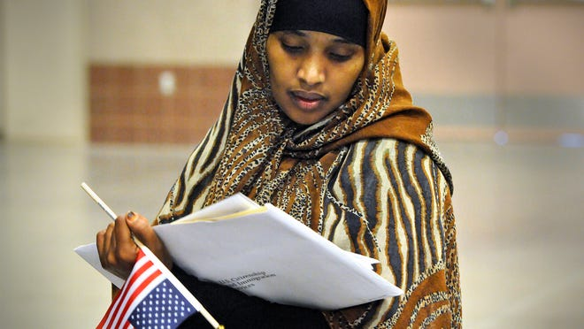 Hodan Mahad Adan looks at her Certificate of Naturalization following Wednesday's ceremony at the River's Edge Convention Center in St. Cloud. Eighty-four people from 34 countries became citizens during the ceremony.