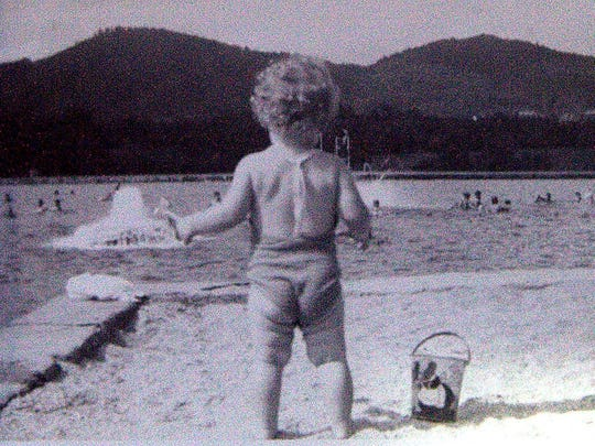 Nancy Baird Fortson, 2 years old, gazes from the Beaver Lake beach toward its swimming pool, circa 1940.