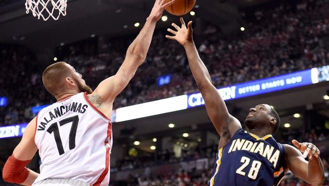 Toronto Raptors' Jonas Valanciunas (17) swats the ball away from Indiana Pacers' Ian Mahinmi (28) during the first half in Game 1 in the first round of the  NBA basketball playoffs in Toronto, Saturday, April 16, 2016.
