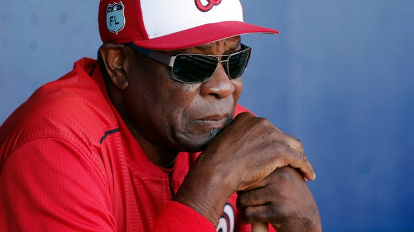FILE - In this March 11, 2017, file photo, Washington Nationals manager Dusty Baker (12) talks to reporters in the dugout before playing New York Mets in a spring training baseball game, in Port St. Lucie, Fla. With Dusty Baker entering his second season as Washington's manager, and standouts such as Cy Young Award winner Max Scherzer, MVP runner-up Daniel Murphy and Rookie of the Year runner-up Trea Turner on the roster, the expectations _ internal and external _ are high, once again, for the Nationals. (AP Photo/John Bazemore, File)