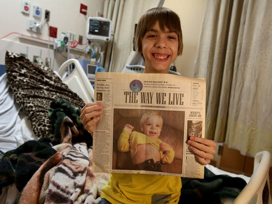 Sitting in a hospital bed at C.S. Mott Children's Hospital in Ann Arbor on Saturday, January 10, 2015, Kaden Cook, 14, of Sault Ste. Marie, Michigan shows off a copy of the features section of the Detroit Free Press from October, 22, 2002 when he was featured in a series of stories and pictures in the paper.