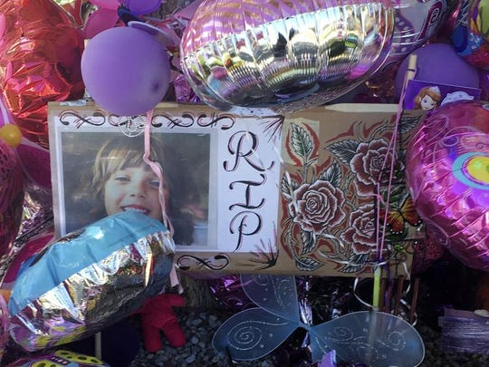 A picture of Victoria Martens, a 10-year-old Albuquerque girl brutally murdered last week, is placed in a memorial outside her former Albuquerque apartment on Monday, Aug. 29, 2016. Stricken with grief, the grandparents and other family members of Martens, who was brutally slain last week, clutched one another and wept Monday as they made their first public comments and thanked the community for its outpouring of love and support.