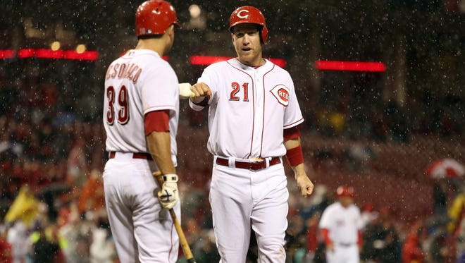 The Reds' Devin Mesoraco bumps fists with teammate Todd Frazier after Frazier scored on a home run by Ryan Ludwick during the 4th inning Monday at GABP.