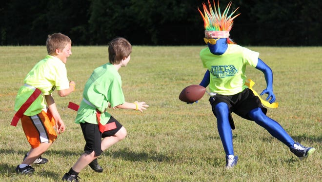 The MEGA Sports Camp mascot plays flag football with participants.