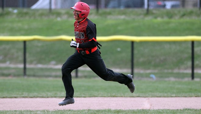 Franklin's Frankie Santiago runs into second base after hitting a double against East.