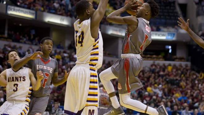 Bosse's Mekhi Lairy (2) goes strong to the hole against Marion's Jordan Smith (14) during the 3A state championship game at Bankers Fieldhouse in Indianapolis Saturday night.