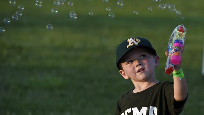 Collin Voyles, 3, of Owensboro, launches bubbles with a bubble gun while attending the Henderson County Fair at the fairgrounds Wednesday.