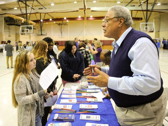 Larry Tutt answers a question from a high school student about his position at Henderson Community College during the high school's CTE Business Fair  in 2015.