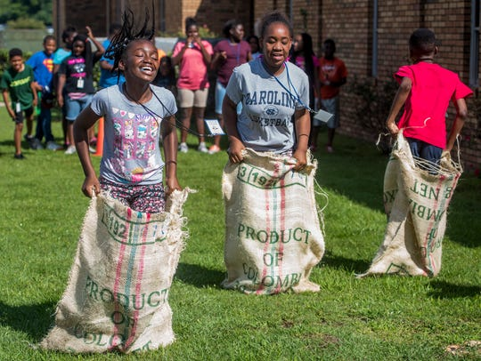 Sixth-grade students participate in a sack race as