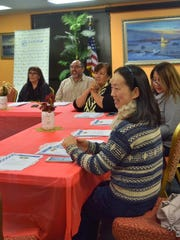 Xiaoyan Luo, right, and other participants listened to cooking instructors.