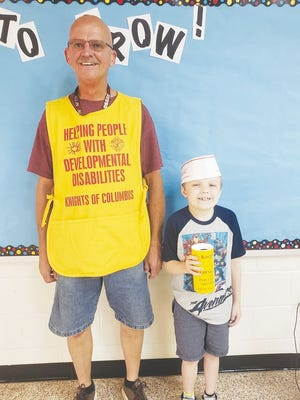Knights of Columbus Chairman Kevin Connelly stands with Quentin Southard at school.