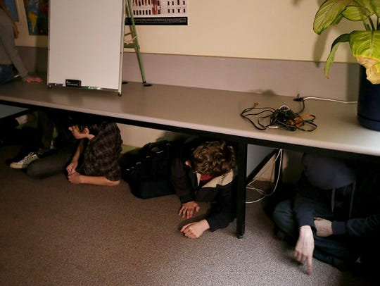 Students take shelter underneath a counter as they take part in a drill simulating an armed intruder at Central Kitsap High School. The Central Kitsap School District has implemented the ALICE program, which stands for Alert, Lockdown, Inform, Counter, Evaluate.