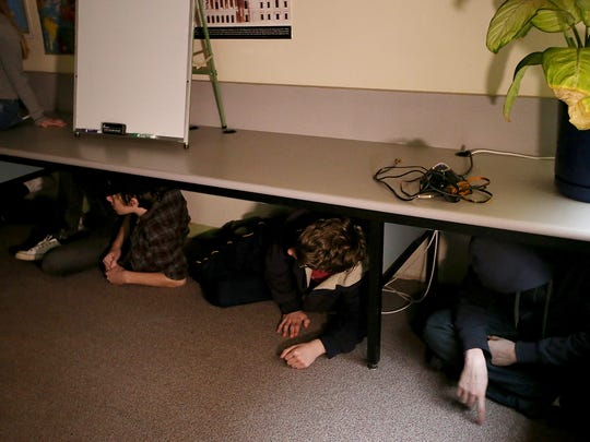 Students take shelter underneath the counter as they take part in an ALICE drill at Central Kitsap High School in Silverdale in 2018. While safety experts offering training in the South Kitsap School District advocate locking down, their philosophy on training with an active shooter differs.