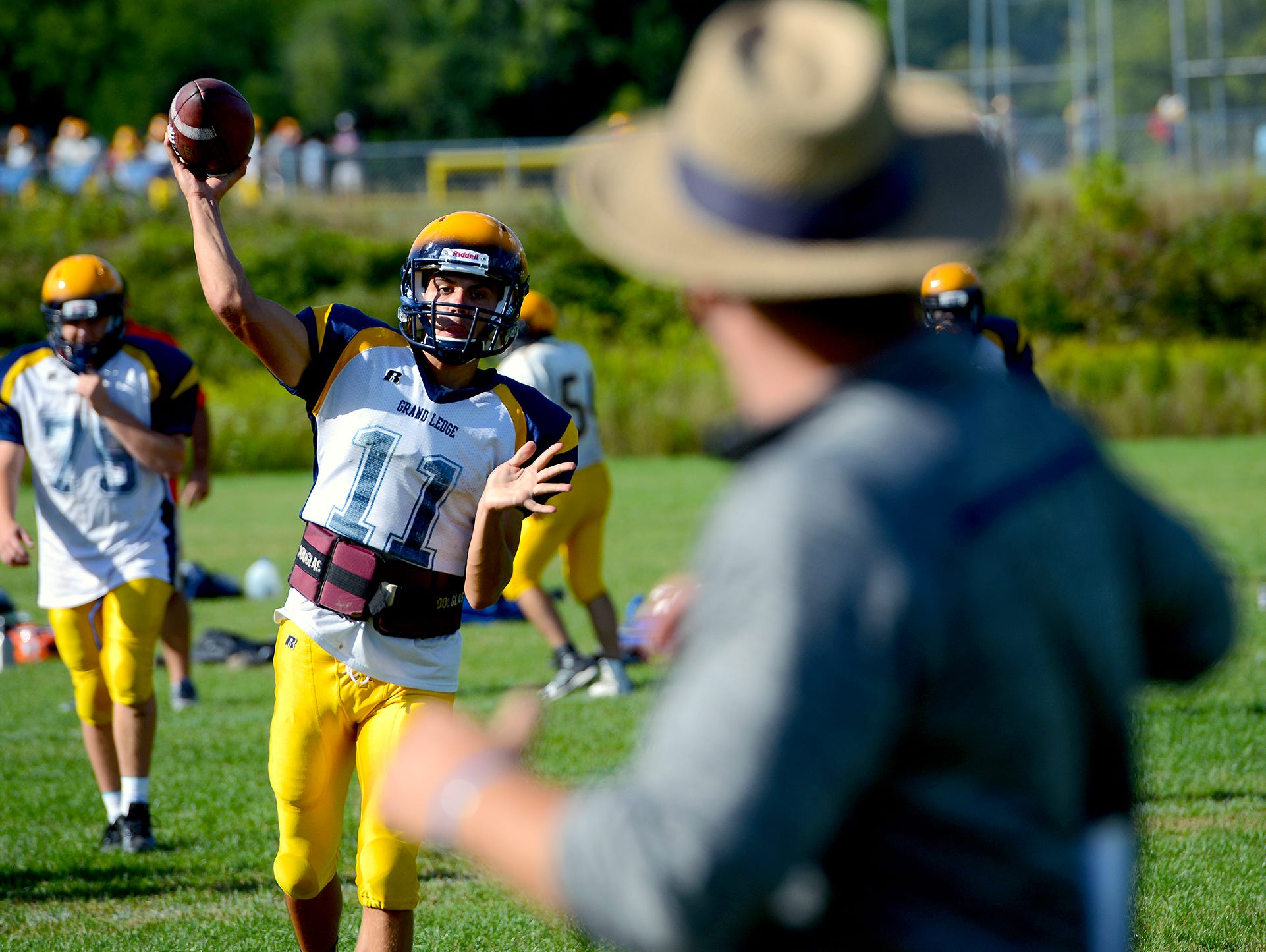 Grand Ledge quarterback back Nolan Bird goes through passing drills working on quick throws and plays with his father, and head coach Matt, at practice Monday.