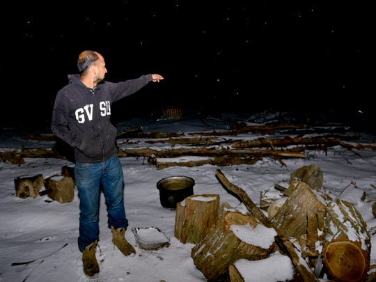 As snow falls and night sets in, Bhim Dahal shows off some of his farmland with the remnants of trees he cleared from the fields on Dec. 8, 2016 in Mason. Dahal, a Nepali Hindu, came to Lansing as a refugee in 2010.