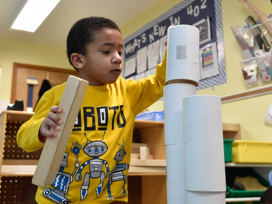 A student plays with cylinders and building blocks at Appoquinimink Preschool Center in Middletown.