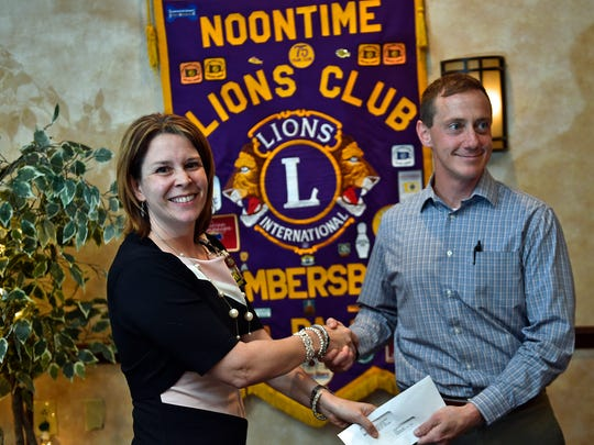 Elyse Fisler, vice president of patient services, Summit Health, presents a $400 donation to  John Nogle of Chambersburg Noontime Lions Club, Tuesday, May 23, 2017 at The Orchards. Summit donated the money after reading about thieves who broke into a trailer and stole prizes intended for Lions Club Trout Derby winners.