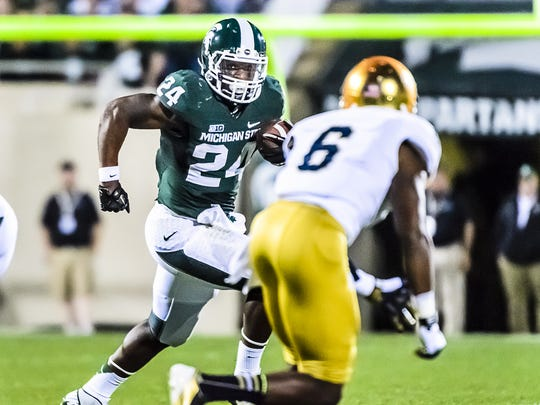 Le'Veon Bell (left) of MSU turns the corner while being pursued by KeiVarae Russell of Notre Dame in the 1st quarter of their game Saturday, September 15, 2012, in East Lansing.