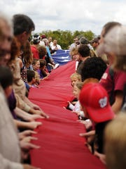 Participants roll out a large American flag during