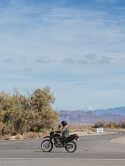 A motorcyclist drives the road near historic Death Valley Junction.