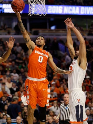 Syracuse's Michael Gbinije goes up for a basket against Virginia's Anthony Gill during the first half of a college basketball game in the regional finals of the NCAA Tournament, Sunday, March 27, 2016, in Chicago.