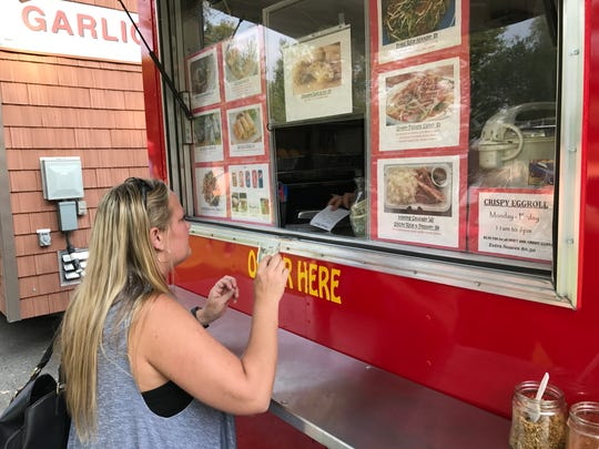 Heather Marshall of Redding orders egg rolls and fried rice with chicken from a food truck at Anderson River Park.