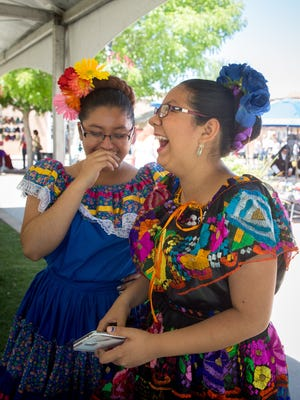 14-year-old Ballet Folklorico de la Tierra del Encanto dancers Erianeley Melendez, left, and Valerie del Plain, joke with each other before starting their performance at the 2016 Cinco de Mayo fiesta on the Mesilla Plaza.