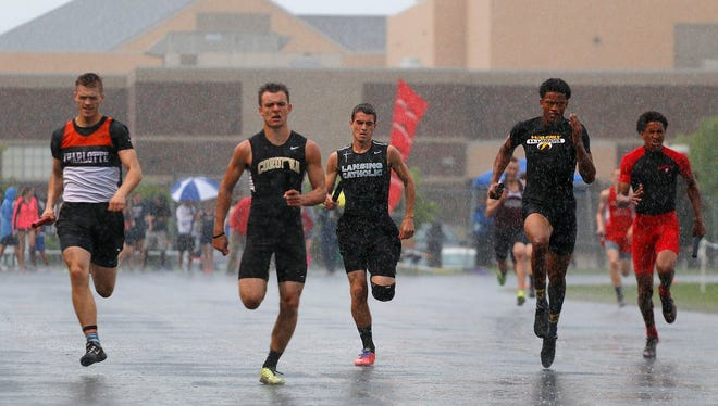 Runners compete in the 800 meter relay in a downpour during the Honor Roll track meet Tuesday, May 26, 2015, at Holt High School in Holt, Mich.