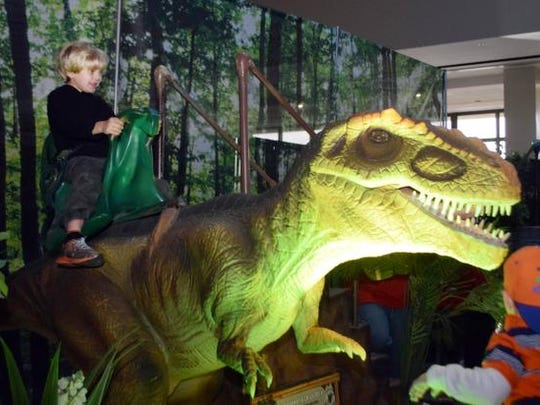 "Pershing Beck, 6, rides a dinosaur at the ""Discover The Dinosaurs"" exhibit at the Alexandria Riverfront Center. The exhibit continues from 10 a.m. to 7 p.m. Sunday."