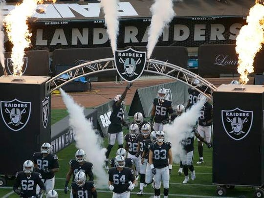 Oakland Raiders players run onto the field before an NFL preseason football game against the Seattle Seahawks in Oakland, Calif., Thursday, Aug. 31, 2017. (AP Photo/Jeff Chiu)