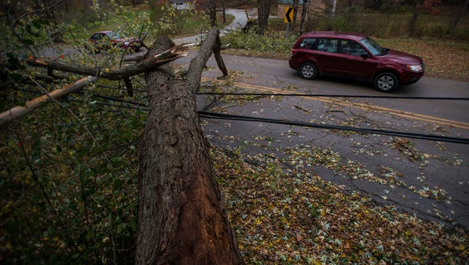 Cars take turns driving around a downed tree and under  the utility lines caught underneath, resting about about 6 to 8 feet above Pond Road in Hinesburg on Tuesday, Oct. 31, 2017. Crews across Vermont are struggling with the sheer volume of damage caused by Monday's windstorm.