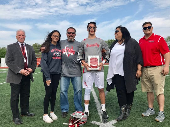 Fair Lawn senior Joe Covino accepts a plaque after becoming the school's No. 1 score. Covino is surrounded by his parents and sister, by principal James Marcella (far left) and coach Scott Leathem (far right).