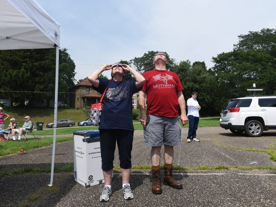 Dan Beebe and his wife Kris look at the eclipse at the Muskingum Valley Council of the Boy Scouts of American in Zanesville on Monday.