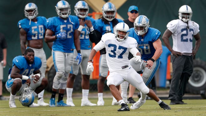 Indianapolis Colts running back George Winn (37) runs by Detroit Lions middle linebacker Paul Worrilow (58) during their training camp practice at the Colts complex on West 56th Street Friday morning August 11, 2017.